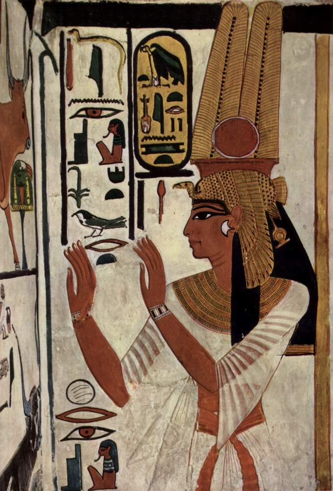 Wall painting depicts Nefertari. Her face is in profile view and she wears a tall elaborate gold hair covering. Her body is in frontal view. Her arms are raised in front of her.