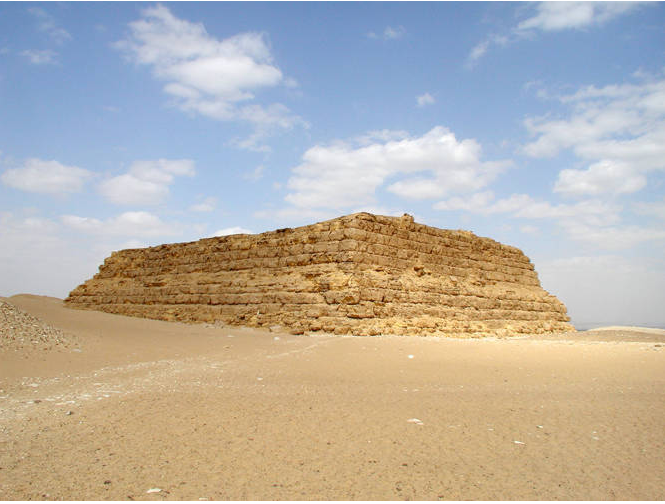 Color photograph depicts flat-roofed, rectangular structure with inward sloping sides, constructed out of mud-bricks.