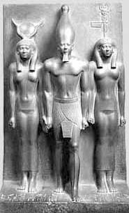 Sculpture depicts a frontal view three figures. A male figure in the middle wears tall cone-shaped headpiece. He wears only a loincloth. He is flanked by two nude female figures.