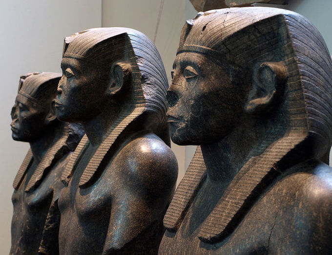 Sculpture of three pharaohs in profile view. All are shirtless and wearing head crowns.