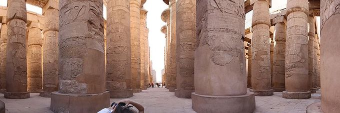 Panoramic photo depicts the ruins of the great hypostyle hall. The roof, now fallen, was supported by 134 columns in 16 rows; the 2 middle rows are higher. The photograph shows several of rows of the columns.