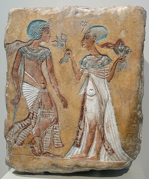 Painted relief depicts a man and a woman walking in a garden. Each wears a blue cap and is dressed in white, the man wears a long skirt, the woman wears a dress. Both wear jewelry on their necks. The woman holds flowers. The man holds a staff or walking stick.