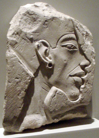 Relief portrays a profile view of Akhenaten's face. He has a prominent chin and wears an earring and pharaoh's head piece.