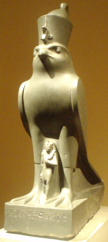 Sculpture depicts the pharaoh in miniature standing between the legs of a life-sized falcon.