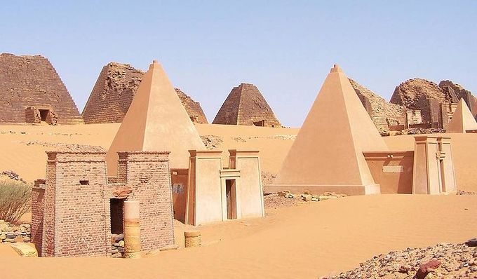 Photo depicts pyramids in the desert of Sudan. They hey are built of stepped courses of horizontally positioned stone blocks. They are tall, narrow structures with a 70-degree incline.