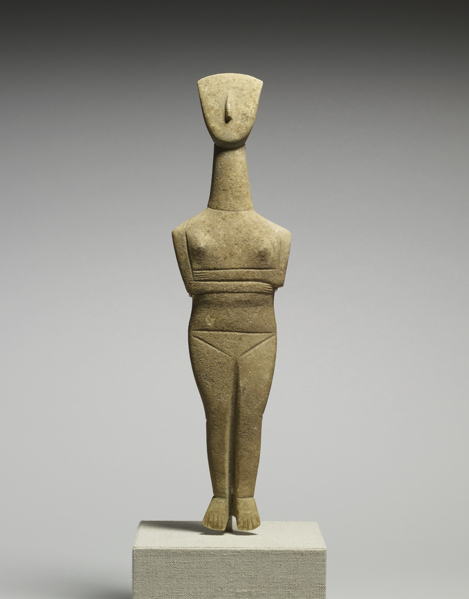 This is a color photograph of a Cycladic female figure, made of marble. It is from the Cyclades, Greece, circa 2500 BCE. The woman is sculpted with her legs together and arms folded over her abdomen, with her breasts and pubic region emphasized.