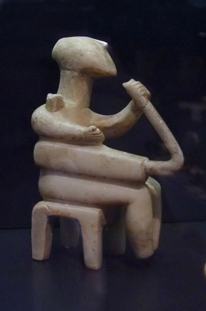 This is a color photograph of a Cycladic male figure playing the harp. It is made of marble and comes from Santorini, Greece, circa 2500 BCE.