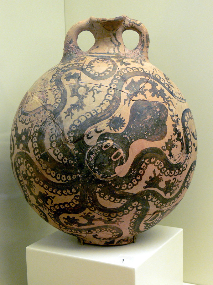 This is a color photograph of a pottery jug or vase. Its surface is covered by an octopus; bits of seaweed fill the negative space.