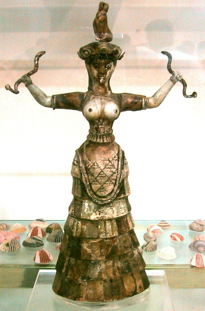 This is a color photograph of the Snake Goddess figurine. It depicts a woman with open arms who holds a snake in each hand, with a feline sitting on her head. She is dressed in a common Minoan style of clothing, a full skirt and a tunic opened at the chest to reveal her breasts.