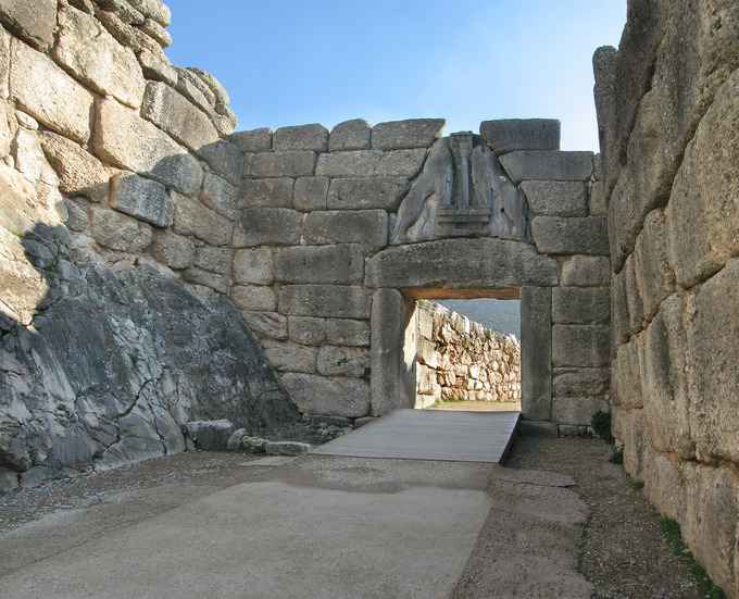 Color photo depicting a stone wall with an archway formed by two large stone pillars capped with a horizontal support. Atop the support, there's a relief of two lions facing one another.