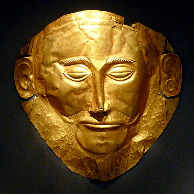 This is a color photo of a gold mask depicting Agamemnon's face. His eyes are closed and his brows are thick and prominent. He has a thin, narrow nose and a moustache.