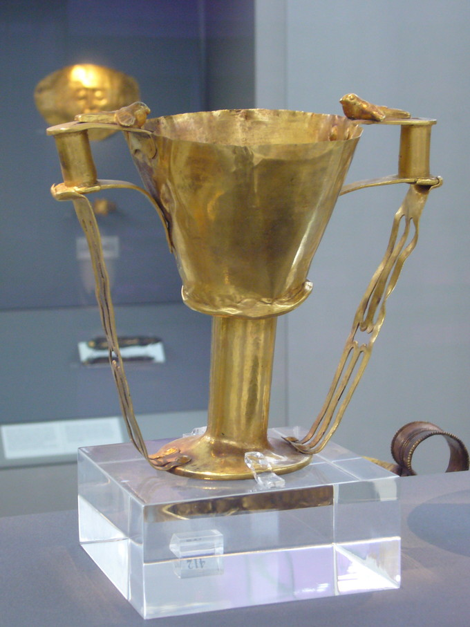 Color photograph of golden goblet with handles. There is a small bird perched on each handle.