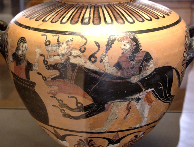 This is a photo of a pot painted with a scene of Hercules bringing Cerberus to Eurystheus. Cerberus is depicted as a black hound-like monster (a hydra) with multiple heads.
