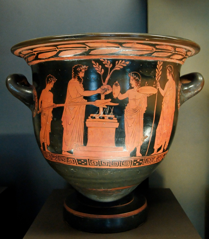 This is a photo of a krater with depiction of a scene of a sacrifice. Greeks dressed in togas and leaf crowns present a small animal to the gods.