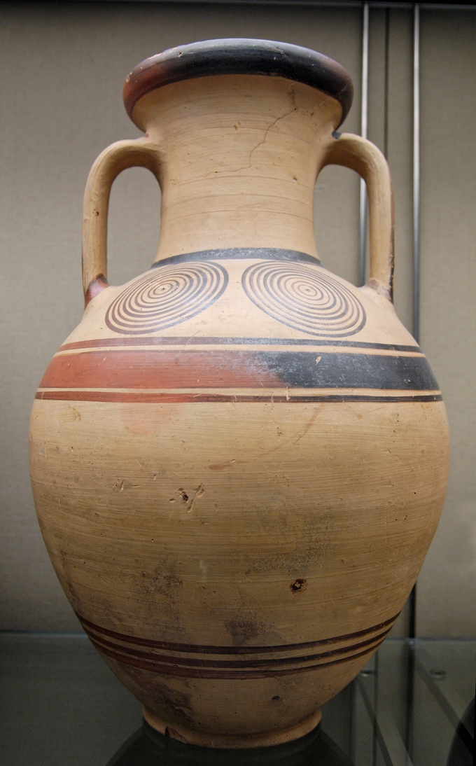 Photo of a tall jar with two handles and a narrow neck. It is decorated with two geometric circles.