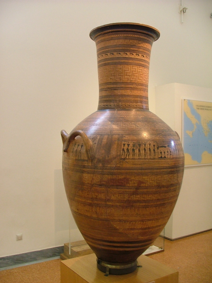 Color photo shows a Greek amphora ( a tall jar with two handles and a narrow neck). It is decorated with a variety of geometric patterns.