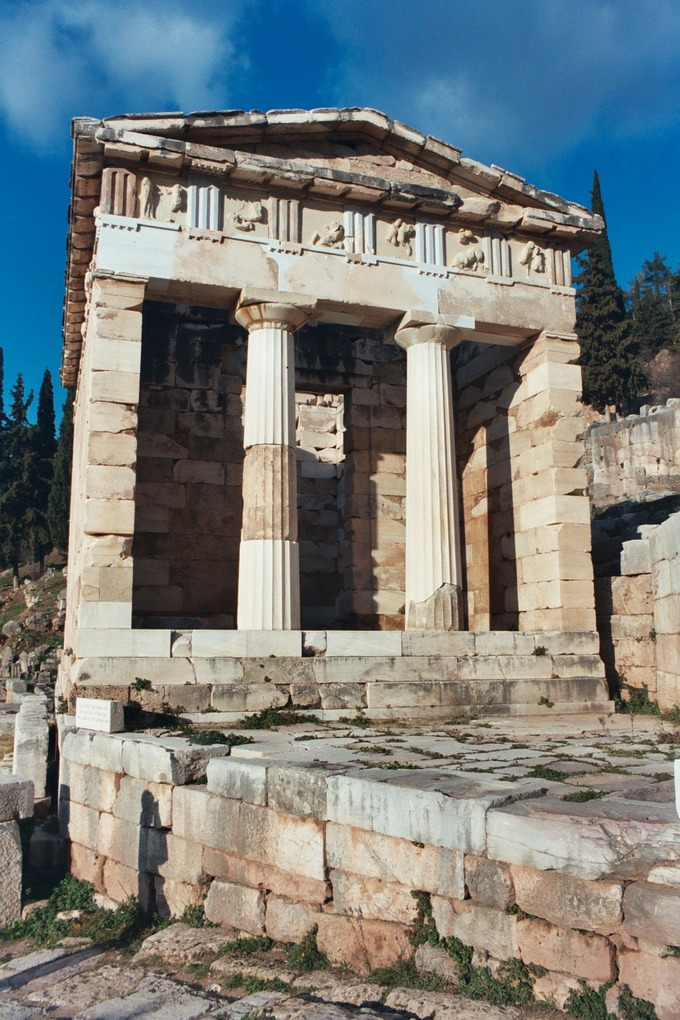 This is a color photo of the current-day exterior of the Athenian Treasury in Delphi, Greece. It is a columned structure with marble pillars.