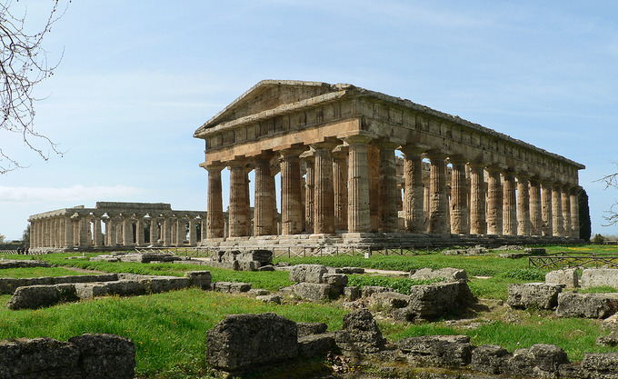 This is a color photograph of the Temple of Hera II and Temple of Hera I, in Paestum, Italy. It shows the columns and foundations of the structures.