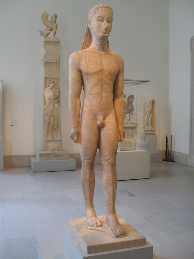 Color photograph of a marble statue of nude male Greek youth. The youth stands straight with his hands at his side and either wears a headpiece or has stylized hair.