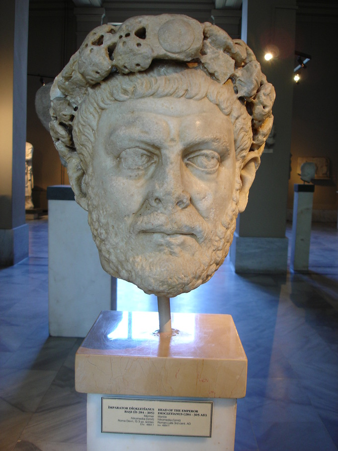 This is a photo shows a Portrait of Diocletian in a museum case. Diocletian achieved stability by establishing the Tetrarchy, Greek for rule by four.
