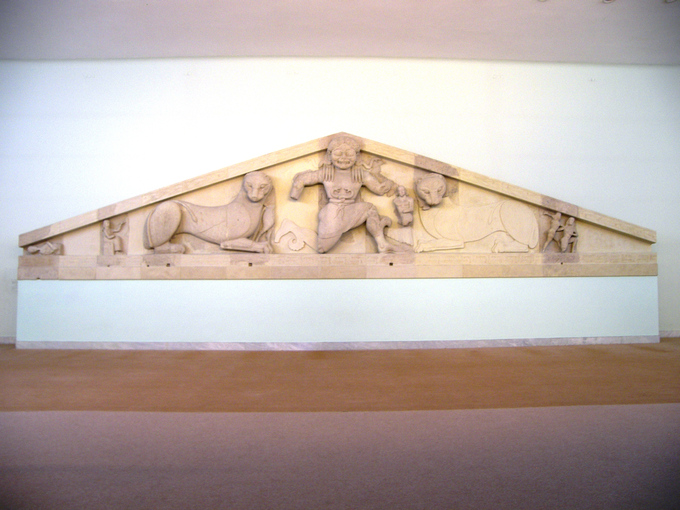 Photo of pediment depicting Medusa in a formulaic, stylized fashion. There are two snakes wrapped around her waist like a belt. She is flanked by panthers.