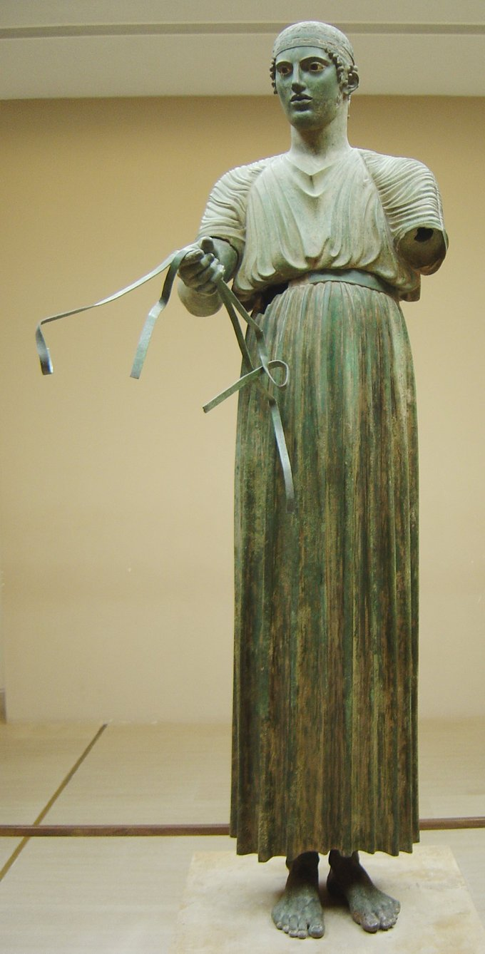 This is a photo of the bronze statue the Charioteer of Delphi, a free-standing charioteer wearing a dress and holding what appears to be the reigns that were attached to the horses that were originally part of the statue.