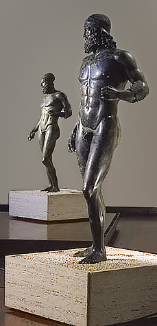This is a photo of the Riace Warriors. Warrior A is on the right and Warrior B on the left. They are made of bronze and appear nude with idealized bodies, including prominent chiseled abdominal muscles. Both wear helmets.