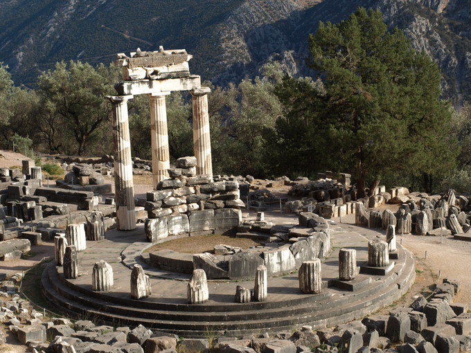 This is a photo of the ruins of the Tholos of Athena Pronaia at Delphi. It shows the unique circular shape of the building's foundation as well as the twenty Doric columns supporting frieze with triglyphs and metope.