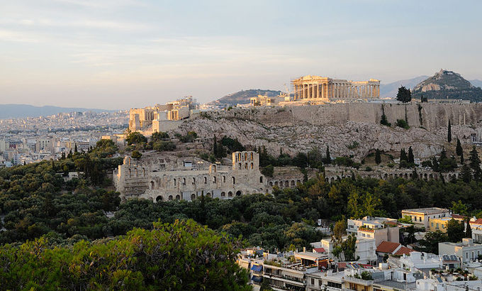 A current-day color photo of the ruins of the Acropolis at Athens. It shows the ancient citadel located on an extremely rocky outcrop above the city of Athens, containing the remains of several ancient buildings of great architectural and historic significance, the most famous being the Parthenon.