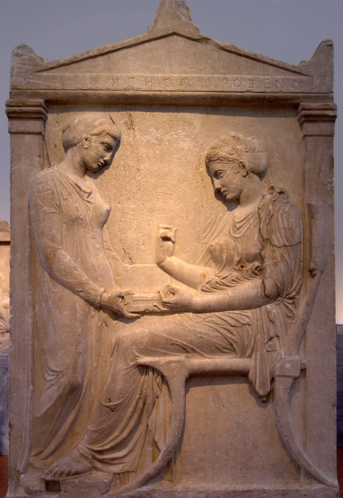This is a photo of the Grave Stele of Hegeso, which depicts two women in draped garments. One woman is seated and the other stands before her, placing a square object in her lap.