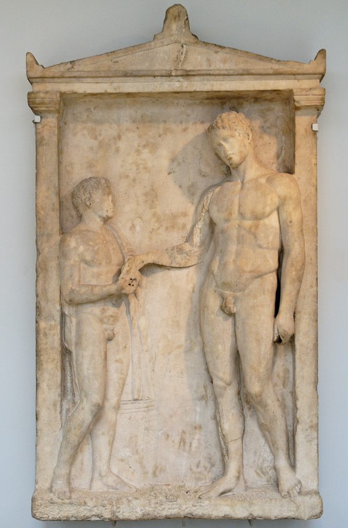 This is a photo of the Grave Stele of an Athlete, which depicts a young nude attendant and a much taller nude athlete, cocking his head and reaching for something that the attendant is holding.