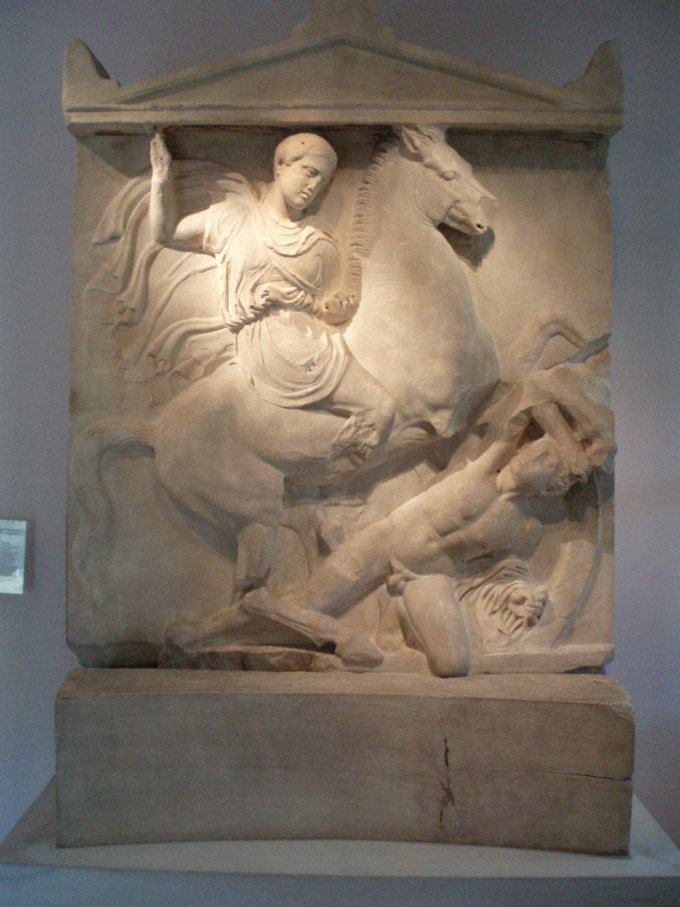 This is a photo of the Grave Stele of Dexileos, it depicts Dexileos on his horse, right arm raised his spear bears down on his enemy (who has a hole bored in his neck).
