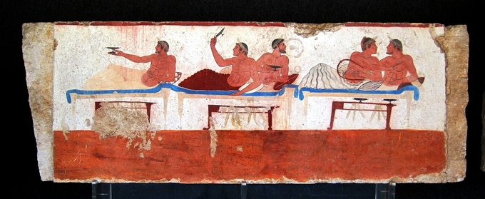 This symposium-scene fresco depicts five individuals on the couches on each wall, there is a single man on the left couch and the other two couches are occupied by two people. Each of the figures is covered to the waist, and they are all crowned.
