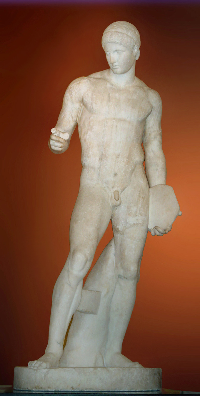 This is a photo of Discophoros. It is a marble statue of a nude male figure with an idealized body (i.e., extremely defined muscles). Her gazes downward and raises an index finger, pointing.