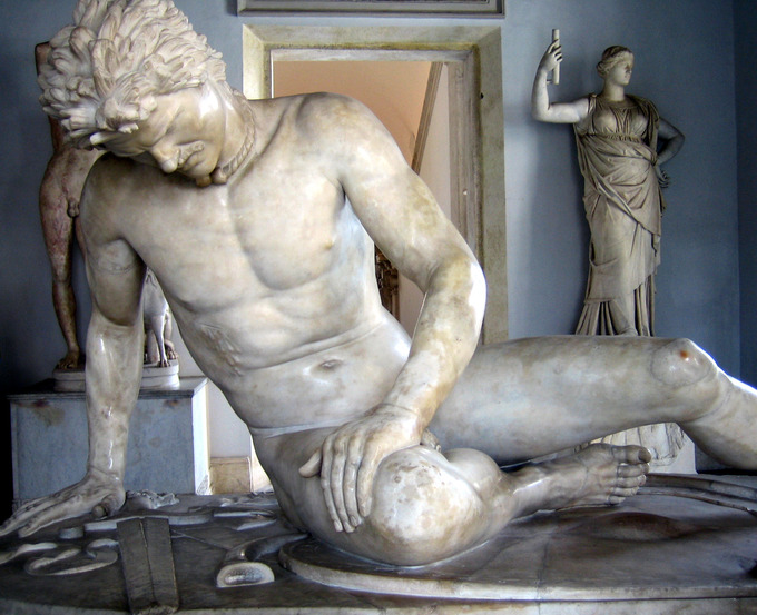 This is a photo of the Dying Gaul. The white marble statue depicts a wounded, slumping male figure. A bleeding sword puncture is visible in his lower right chest.