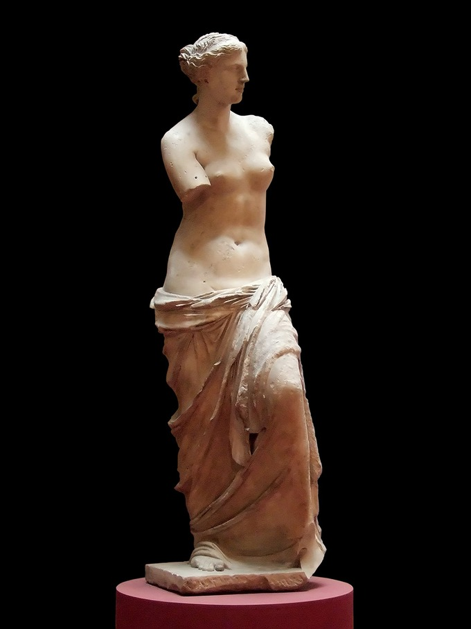 This is a photo Venus de Milo, and it is believed to depict Aphrodite, the Greek goddess of love and beauty. The statue depicts a woman's face in profile view and a body in frontal view. She is nude from the waist up. She has idealized abdominal muscles, and her lower body is clothed in draped fabric. She is missing both her arms.