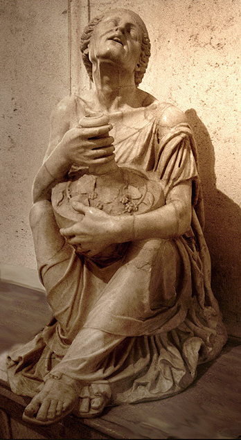 This is a photo of the Drunken Old Woman. The sculpture depicts an old woman squatting on the ground holding a container in her lap.