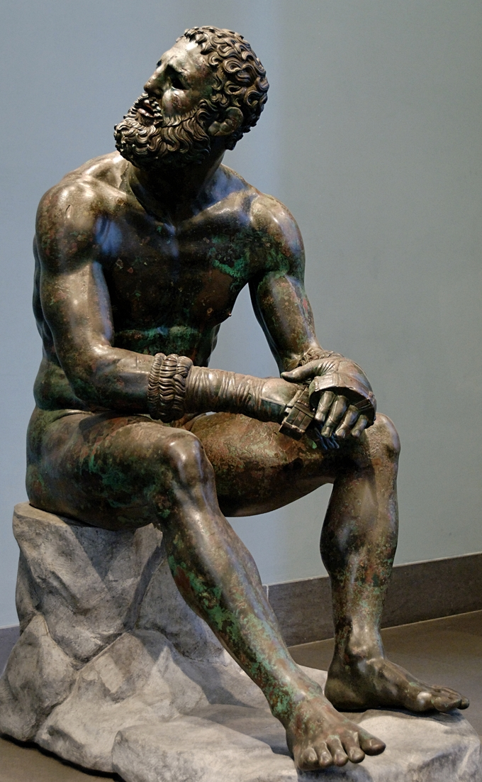 This is a photo of the bronze statue, Seated Boxer. That statue depicts a sitting nude boxer at rest, still wearing his caestus, a type of leather hand-wrap. He appears to be looking up and behind him.