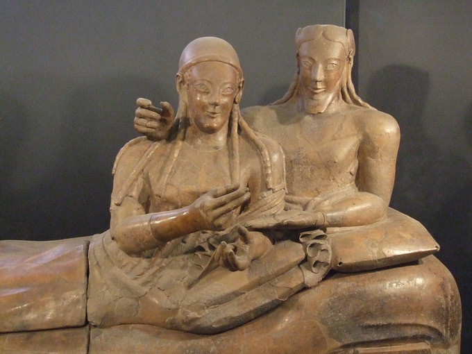 This sarcophagus depicts a man and woman sharing a banquet couch. They are both smiling and expressing affection. She is in gesture of offering something to him and he is making a gesture of receiving it. They both have almond-shaped eyes and long braided hair.
