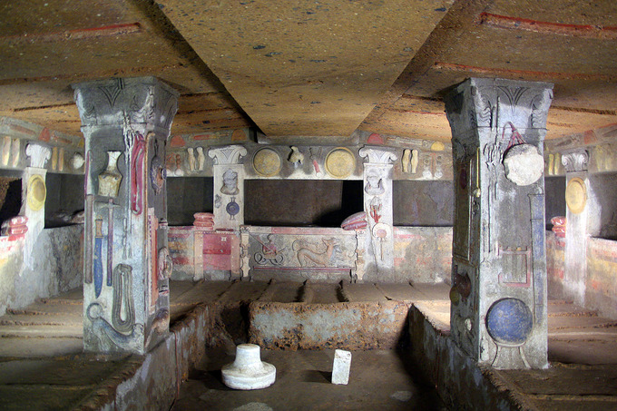 This is a photo of the interior of the Tomb of the Reliefs. The walls and the two freestanding pilasters are decorated with stucco reliefs of objects from daily life. These include household items, pets and other animals.