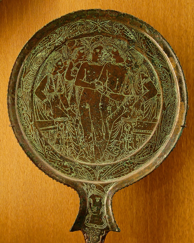 This is a photo of an Etruscan bronze mirror with an engraving of the Judgment of Paris, which depicts a contest between the three most beautiful goddesses of Olympos--Aphrodite, Hera and Athena. They compete for a golden apple.