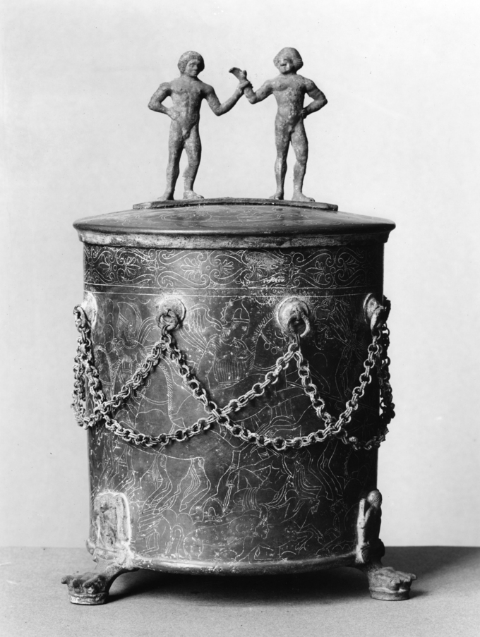This is a photo of a cista ( a bronze circular container with a lid used to store goods). The handles are nude male statuettes.The cista is engraved with battle scenes between the Etruscans and the Gauls and decorated with a criss-crossed chains.