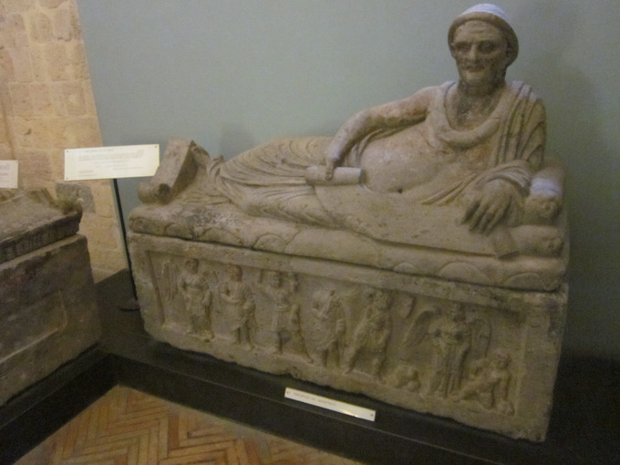This is a photo of the Sarcophagus of Lars Pulena. The sculpted scene on the front of the coffin shows the deceased in the Underworld between two Charuns. On the lid, Pulena is shown laid across, in a reclining position, resting on his left arm and in front of him, a list of his life's achievements which were inscribed on an open scroll.