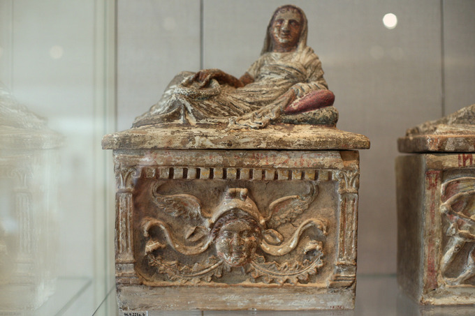 This is a photo of a terra cotta cinerary urn. A depiction of the deceased, an woman, lies across the lid wearing draped clothing that covers her head like a hood. On the bottom is a relief of her face.