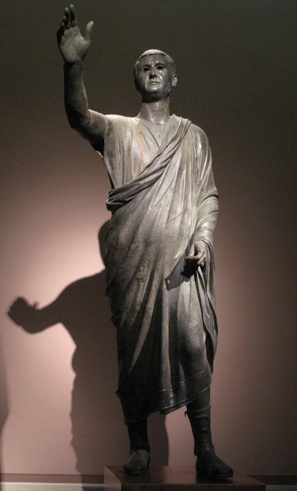 This is a photo of that statue called Aule Metele. It depicts a man wearing a short Roman toga and footwear. His right arm is raised to indicate that he is an orator addressing the public.