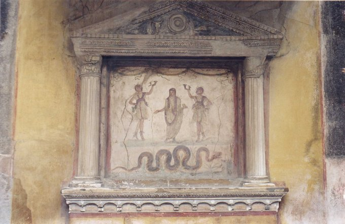 This photo shows a fresco and stucco lararium from the House of the Vettii. Two Lares (guardian deities), each holding a rhyton (cone-shaped drinking container), flank an ancestor-genius holding a libation bowl and incense box, his head covered as if for sacrifice. The snake, associated with the land's fertility and thus prosperity, approaches a low, laden altar.