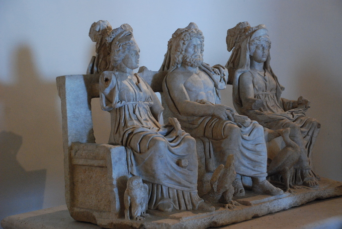 This photo is taken in the Sanctuary of Fortuna Primigenia, in Palestrina, Italy. It shows Juno, Jupiter, and Minerva seated on a bench. Juno and Minerva wear togas and have stylized hair. Jupiter is bare-chested and bearded.