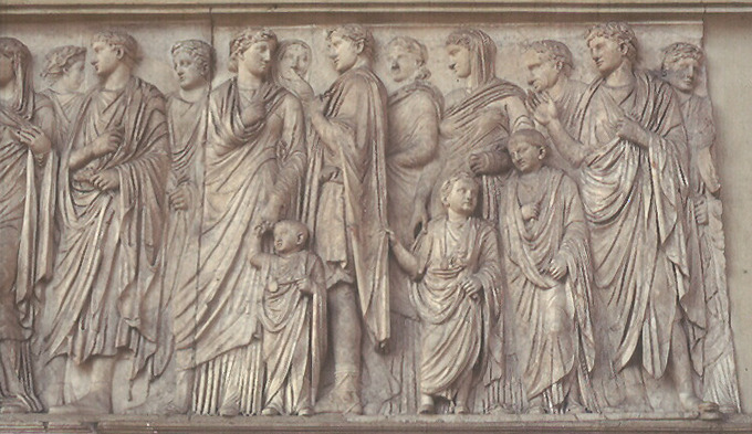 This photo shows a detail from the processional scene on the south wall of the Ara Pacis Augustae. It shows members of the imperial household, including adults and small children. They are dressed tunics and togas.
