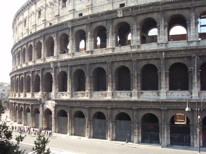 This photo shows the exterior of the Flavian Amphitheater or Colosseum, an oval amphitheatre in the centre of the city of Rome.