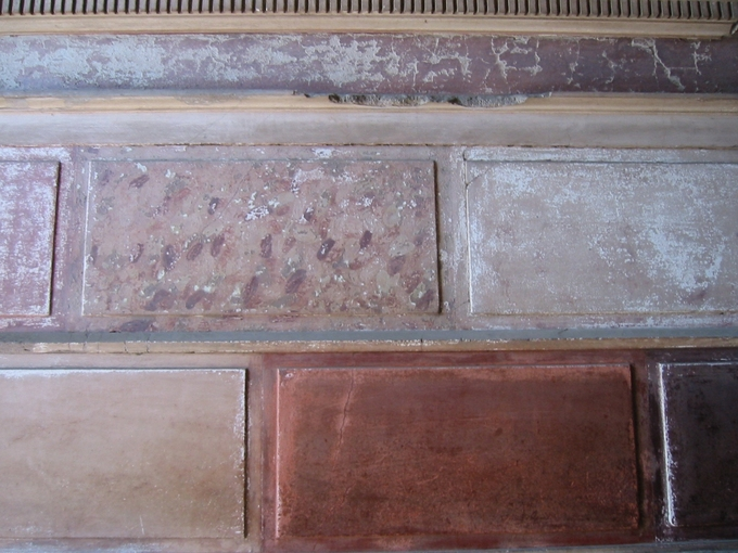 This photo is a closeup of a Pompeiian first-style wall painting, demonstrating the style characterized by colorful, patchwork walls of brightly painted faux-marble.